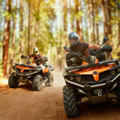 Two atv riders in helmets, speed race in forest, front view. Riding on quad bike, extreme sport and travelling, quadbike offroad adventure